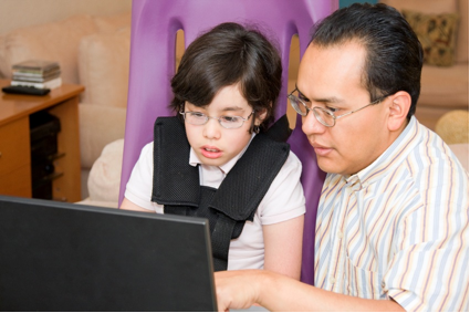 Photo of a boy and man looking at a computer screen.