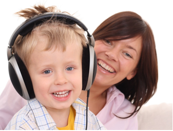 Photo of a little boy, wearing headphones, and a woman.