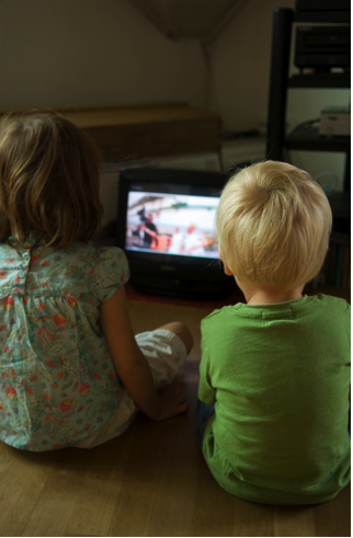 Photo of a young girl and boy watching a portable television.