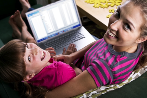 Photo of a girl and a young woman using a laptop computer.